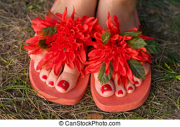 Decorated slippers - Two woman legs decorated red flowers...