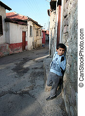poor child in front of his house - A child is standing in...