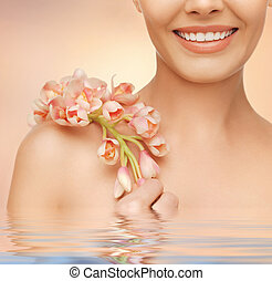 womans shoulder and hands holding orchid flower - closeup...