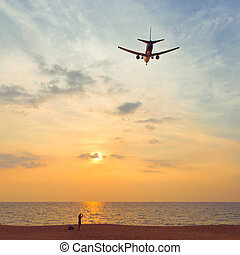 Airplane in the sunset sky - Man on the beach is looking on...