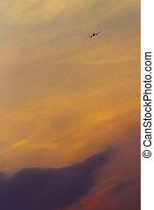 Plane in the sunset sky - Airplane flying to the sunset sky