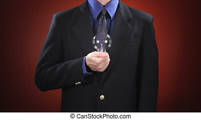 Man Holding Light Bulb - A man in a business suit in front...