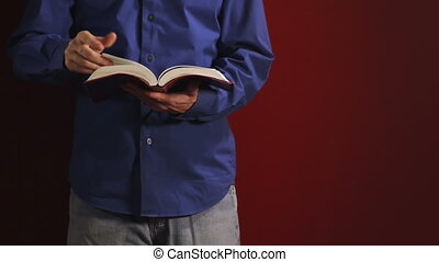 Man Reading Bible - Man leans against a red wall and reads...