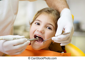 Little girl is having her teeth examined by dentist