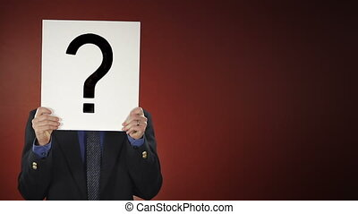 Question Mark Man - A businessman steps into frame holding a...