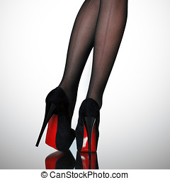 High heels - Slim female legs in dark stockings wearing high...