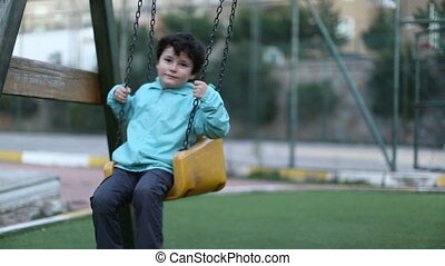 playground - happy boy on a swing, steady cam shoot