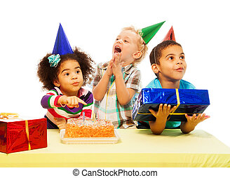 Three kids with birthday cake and peresents