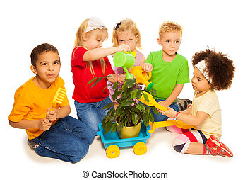 Spring chores - Five little kids playing planting tree and...