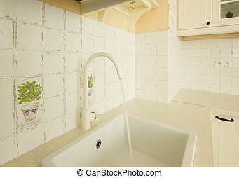 close up of sink with running water in white kitchen in...