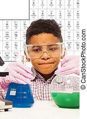 Black little boy experiments with chemistry about to mix two...