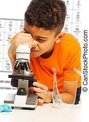 Black boy looking in microscope - Black boy in orange...