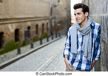 Handsome man with modern hairstyle smiling in urban...