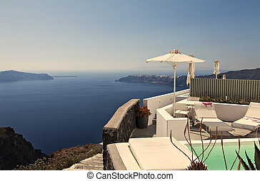 Santorini view - Image of a balcony with sunchairs...