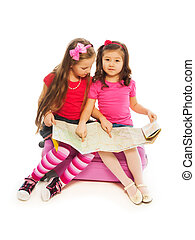 Where are we traveling - Two 6-7 years old girls sitting on...