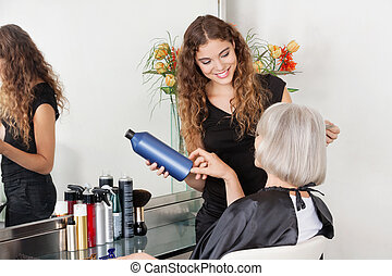 Hairstylist Advising Hair Color To Senior Client - Female...