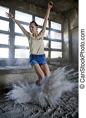 woman jumping in dust - young atractive woman jumping in...