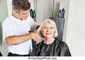 Hairdresser Cutting Senior Client's Hair - Hairdresser...