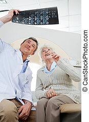 Radiologist And Patient Looking At X-ray - Mature male...