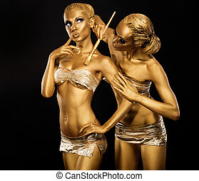 Body Art. Woman painting Body with Paint Brush in Golden...