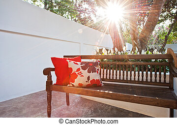 Outdoor patio seating are with nice bench at sunset