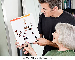 Woman With Male Hair Stylist Selecting Hair Color - Senior...