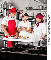 Chefs Using Digital Tablet In Kitchen - Chefs looking for...