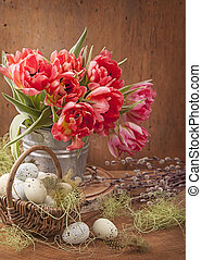 Tulip flowers and easter eggs on wooden background