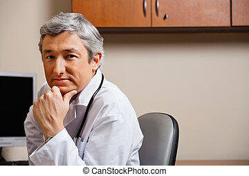 Serious Doctor With Hand On Chin - Portrait of serious...