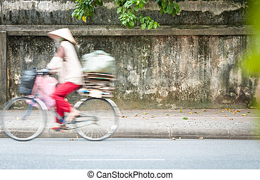 Person riding bicycle on road in Vietnam, Asia.
