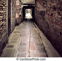 Narrow street in Venice, Italy, ending at a getty in a canal
