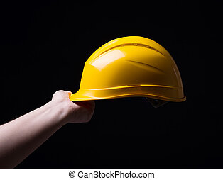 Man with helmet in hand on a black background