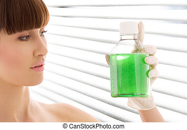 green liquid - female lab worker holding up bottle with...