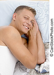 smiling young guy resting in bed
