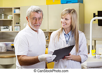 Dentist and assistant - Dentist and his assistant are...