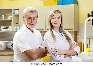 Dentist and assistant - Dentist and his assistant in dental...