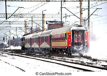 Passenger train passes the snowy line during wintertime in...