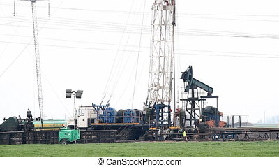 oilfield with drilling rig and pump jack