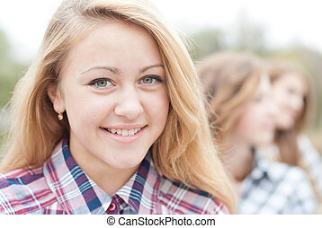 Young happy teen girl with friends closeup portrait