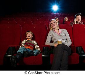 Smiling mother and her son in cinema with other people...