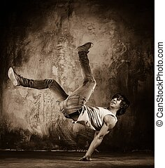 Toned picture of young man doing acrobatic movements against...