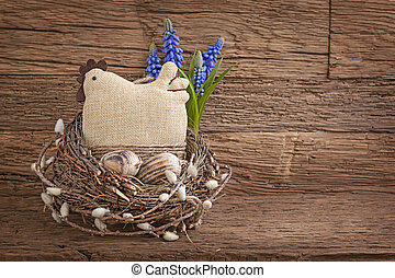Easter eggs and hen in nest on wooden background
