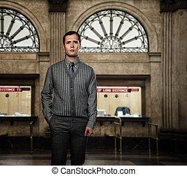 Confident man wearing grey vest and necktie against ticket...