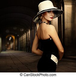 Woman in black dress and big white hat alone outdoors at...