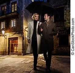 Elegant couple in autumnal coats walking in the rain...