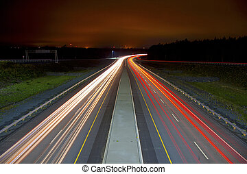 Light Streaks on Highway - Red and white light streaks from...