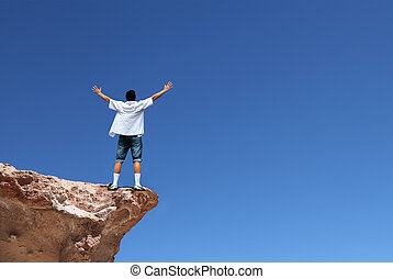 Man on the edge of cliff - Man with arms raised in the sky,...
