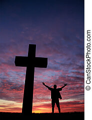Silhouette of a man at the cross - Dramatic sky scenery with...