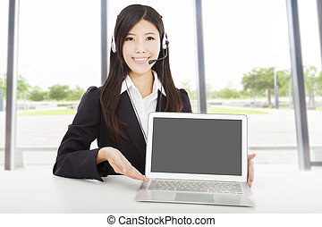 smiling businesswoman with headset and laptop in the office