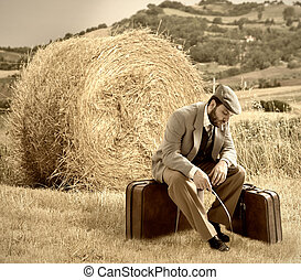 Emigrant man with the suitcases in wheat field